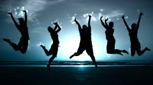 Jumping for joy-5 silhuoettes against dark blue sky