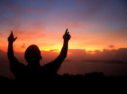 Prayer-silouette man standing hands lifted up to sunrise-sunset